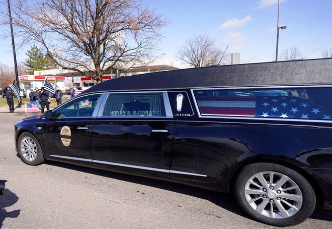 Sebuah mobil jenazah yang membawa peti mati terbungkus bendera dari Boulder yang jatuh, Colorado, petugas Departemen Kepolisian Eric Talley tiba di sebuah upacara peringatan di sebuah gereja pada hari Selasa, 30 Maret 2021, di Lafayette, Colo.