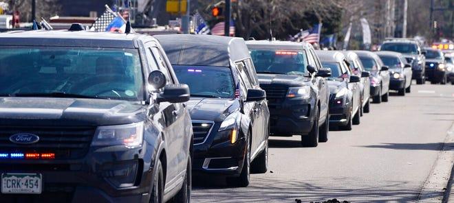 Mobil jenazah yang membawa peti mati Boulder yang jatuh, Colorado, petugas Departemen Kepolisian Eric Talley berada dalam prosesi panjang kendaraan darurat.