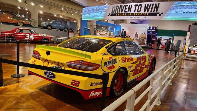 """The entrance to The Henry Ford's """"Driven to Win: Racing in America"""" exhibit. Joey Logano's championship NASCAR from 2018 is featured."""