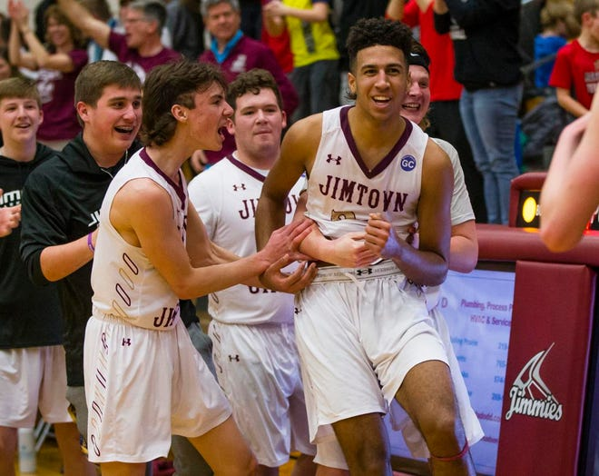 Jimtown's Preston Phillips (24) is grabbed by his teammates after winning a sectional game in March 2020 in Elkhart. Phillips led the team with 14.8 points per game as a senior.