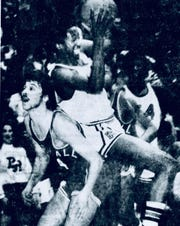 Mike Woodson, Broad Ripple, drives toward the basket over the back of Marshall's Doug Whyde during a game in January of 1976.
