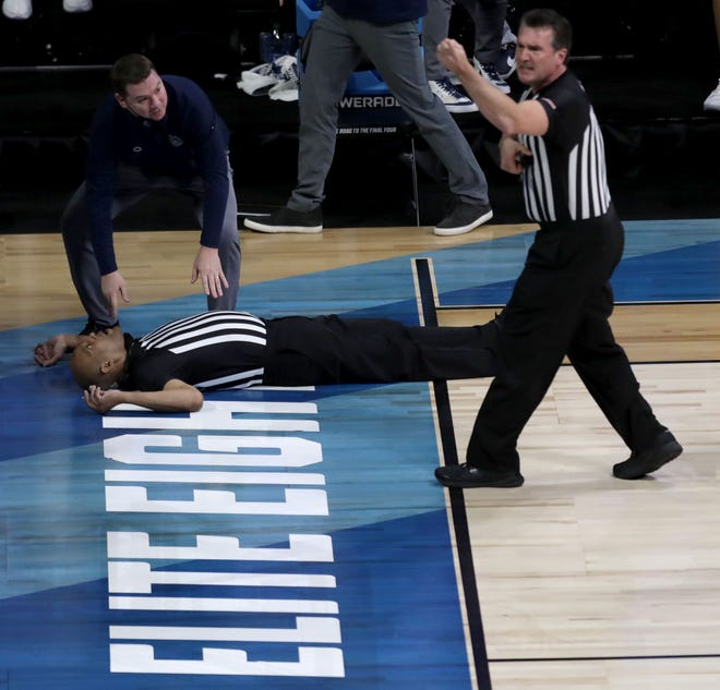Official Bert Smith lies on the court after collapsing during a game between Gonzaga and USC in the Elite Eight round of the 2021 NCAA Tournament on Tuesday, March 30, 2021, at Lucas Oil Stadium in Indianapolis, Ind. Smith was alert when he was taken off the court on a stretcher, and was not transported to a hospital.