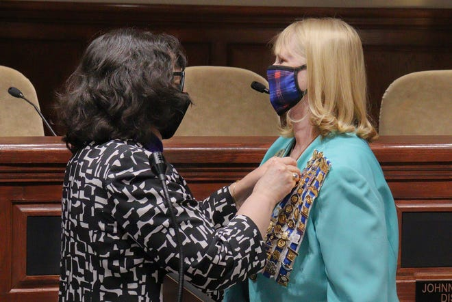 """Local chapter of the Daughters of the American Revolution Regent Beth Bates pins Jackie Utley with the honors of her late spouse, Ralph """"Wolf"""" Lovell Jr., during Vietnam Veterans' Day on Monday in the George A. Smith Meeting Room at Jackson City Hall."""