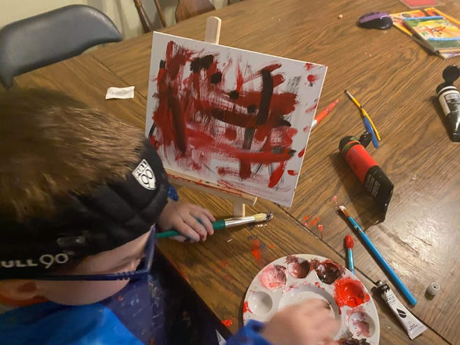 Nickolas Zoesch, 5, of Menomonee Falls, works on a painting for the Greenfield Fire Department. Nickolas has two rare genetic conditions along with hypothyroidism and epilepsy. He was commissioned by the fire department to create paintings for the station's new dorms after Greenfield Fire Chief Jon Cohn saw Nickolas' artwork on Facebook.