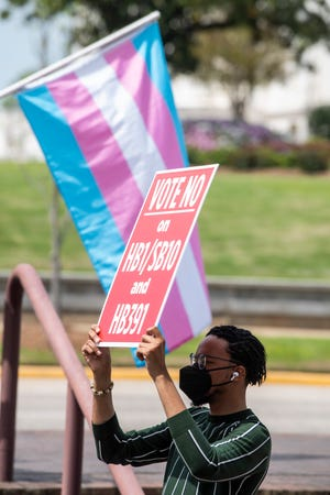 Protesters in support of transgender rights rally outside the Alabama State House in Montgomery, Ala., on Tuesday, March 30, 2021.