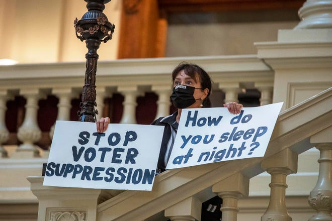 Ann White of Roswell, Georgia, holds protest signs on the North Wing stairs of the Georgia State Capitol building on Thursday, March 25, 2021, in Atlanta. The governor signed into law a sweeping bill that imposes new voting restrictions later Thursday. (Alyssa Pointer/Atlanta Journal-Constitution /TNS)