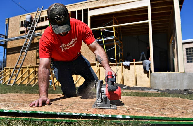 Bryan Irwin of R. Packer Construction cuts plywood at the future site of Comfort Zone Mattress on North George Street in York City, Tuesday, March 30, 2021. The business was displaced from its previous location in August 2019, due to a fire at Yorktown Mall. Dawn J. Sagert photo