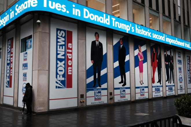 News headlines on the impeachment trial of Donald Trump are displayed outside of the Fox headquarters on Feb. 9, 2021, in New York. (Spencer Platt/Getty Images/TNS)