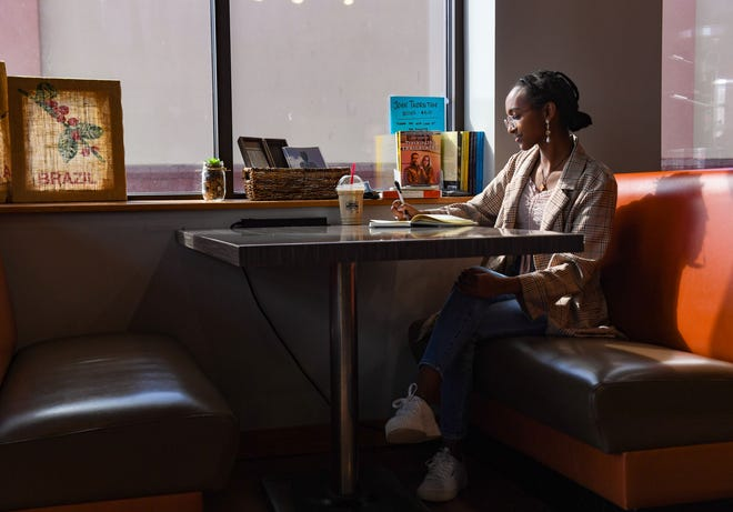 Washington High School senior Rahele Megosha poses for a portrait at her favorite writing spot on Tuesday, March 30, 2021 at Dunn Brothers Coffee in Sioux Falls.