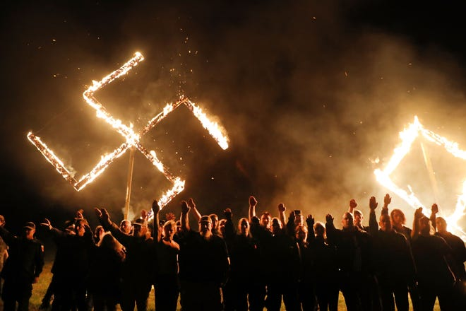 Members  of the National Socialist Movement, one of the largest neo-Nazi groups in the U.S., hold a swastika burning after a 2018 rally in Georgia.