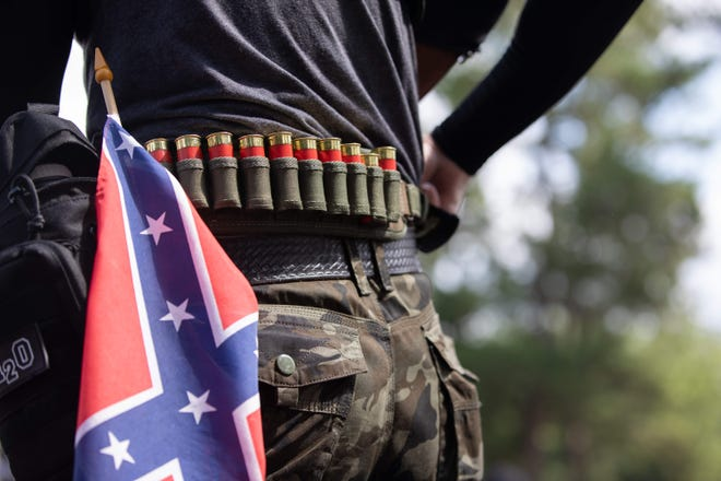 In this file photo taken on August 15, 2020, a man, with ammunition and a confederate flag, takes part in far right militias and white pride organizations rally near Stone Mountain Park in Stone Mountain, Georgia.