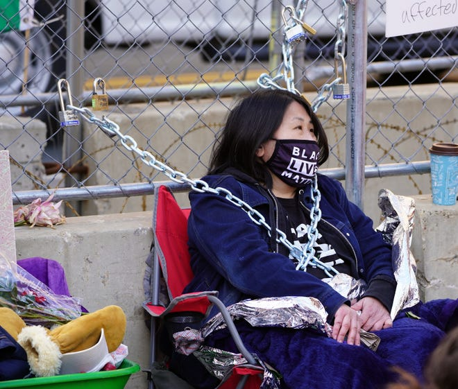 High school English teacher Kaia Hirt, 48, sits wrapped in blankets and heavy chains locked to the security fence surrounding the courthouse where a jury is hearing the case against former Minneapolis police Officer Derek Chauvin, who is accused of killing George Floyd in 2020. Hirt said she locked herself to the fence to get media attention for the need to reform policing and address structural racism across the United States.