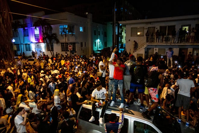 Crowds defiantly gather in the street an hour past curfew in Miami Beach, Fla., on March 21, 2021.