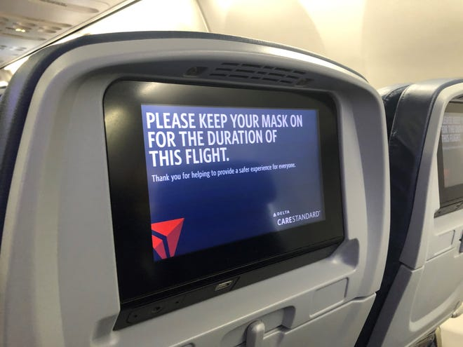 Seatback video screens on Delta Air Lines planes remind travelers that masks are required throughout the flight.
