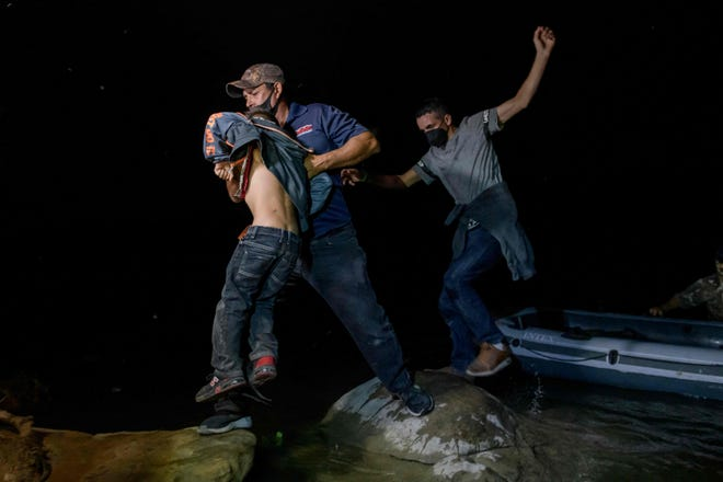 March 29, 2021: Migrants from Central America crossing illegally from Mexico to the US to seek asylum disembark from an inflatable boat on the US side of the Rio Grande river at the border city of Roma on March 29, 2021. (Photo by Ed JONES / AFP) (Photo by ED JONES/AFP via Getty Images) ORG XMIT: 0 ORIG FILE ID: AFP_97222Q.jpg