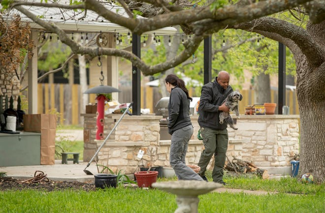 A law enforcement officer carries a dog into a house in the 12000 block of Hero Way West in Leander where 19-year-old is suspected of his killing his mother on Wednesday March 31, 2021.