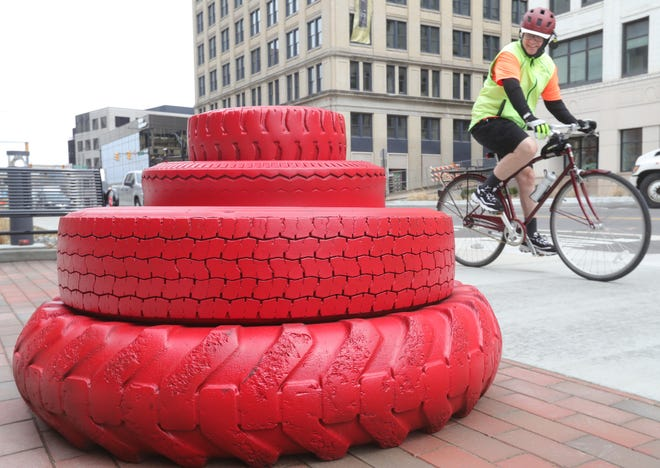 A bicyclist passes a Devo energy dome sculpture made of tires Wednesday in front of the Akron Civic Theatre.