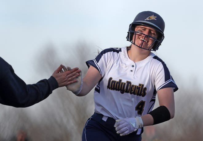 Tallmadge's Zoe Rensel high fives coach Brittany Lightel as she rounds third after hitting a solo homer to left center field during a softball game against Crestwood, Tuesday, March 30, 2021, in Tallmadge, Ohio. [Jeff Lange/Beacon Journal]