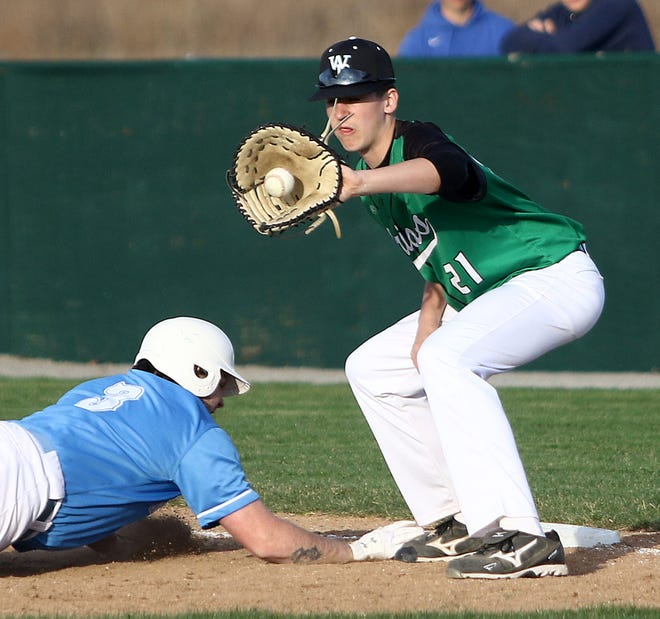 West Branch first baseman Beau Alazaus, right, catches the throw from the mound as Alliance's Corey Prendergast dives back to the bag during league play at West Branch High School Tuesday, March 30, 2021.