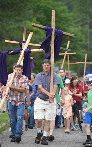 Craig Garner (left) and Louis Hymel (middle) took part in a 2019 Good Friday cross walk in Augusta.