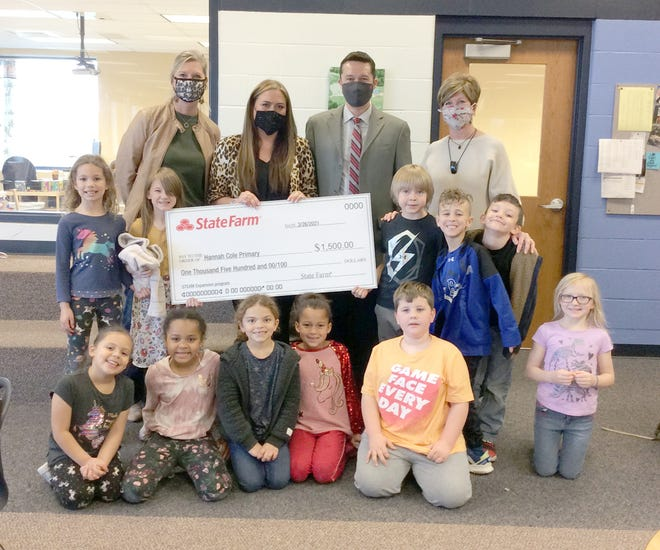 Boonville State Farm agent Jennifer Wesselman (second from left) and State Farm sales leader Ryan Kenney (third from left) visited the school Monday to present a check to school Principal Leslie Reardon (far left), Library Media Specialist Cindy Spaedy (far right) and HCP students.