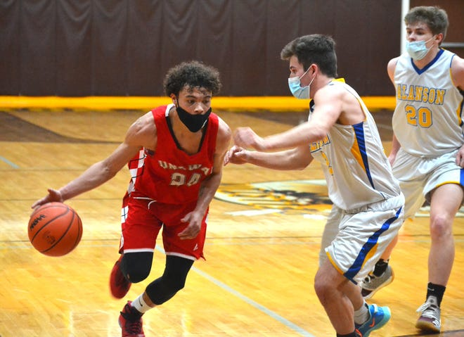Onaway senior guard Kevin Pearson (left) looks to drive past Alanson senior Caleb Corey during the first half of a Division 4 boys basketball regional semifinal in Pellston on Tuesday.