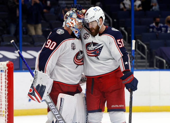 Blue Jackets goaltender Elvis Merzlikins and defenseman David Savard celebrate after defeating Tampa Bay on Tuesday. The win kept the Jackets three points back in the playoff race.