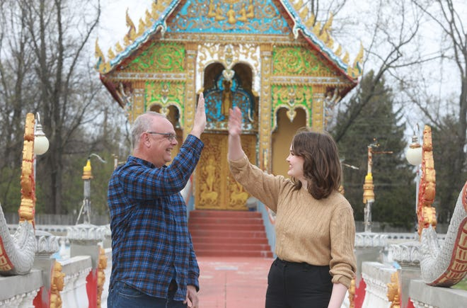 Steve Huggins and his daughter Betsy Huggins celebrate with a high-five at the Watlao Buddhamamakaram, 3624 Bexvie Ave., on the East Side. The Buddhist Temple was the answer to Riddle No. 9 in Joe's Mildly Entertaining Easter Egg Hunt.