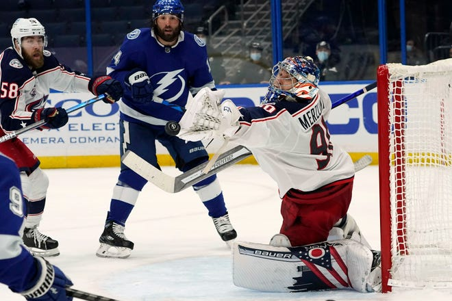 Elvis Merzlikins (90) makes a save as defenseman David Savard (58) and Tampa Bay Lightning left wing Pat Maroon (14) look on during the second period of the Blue Jackets' 3-1 victory Tuesday in Tampa, Fla.