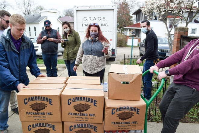 Members of the Guernsey County Young Leaders tally food donation totals as they are dropped off at the Feed My People kitchen on Wednesday. More than 10,000 food items were collected during the recent drive.