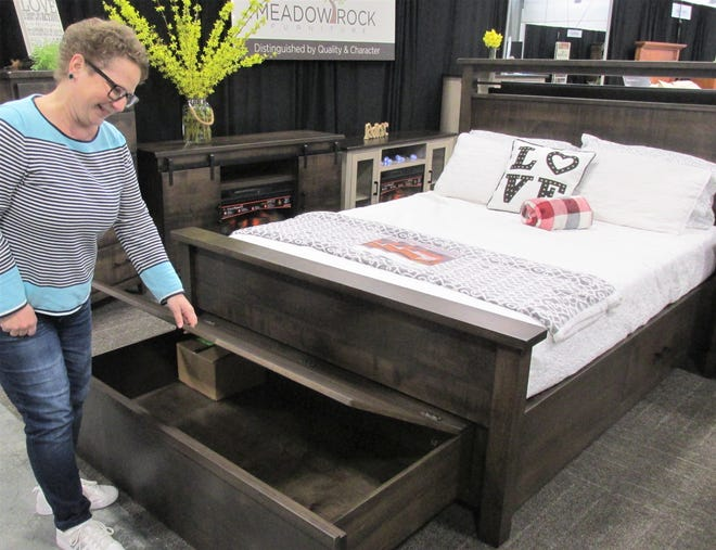 Hardwood Furniture Guild Director Shasta Mast shows a chest drawer that stores under the bed, one of the many new items trending in the furniture industry. This bedroom set was manufactured by Meadow Rock Furniture in Fredericksburg and was part of the display at the Ohio Hardwood Furniture Market held at the Harvest Ridge Expo Center and the Mount Hope Event Center on Tuesday and Wednesday.