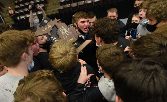 Clinton senior Brayden Randolph celebrates with his teammates in a huddle after winning the Division 4 team state championship Tuesday night at the Wings Event Center in Kalamazoo.