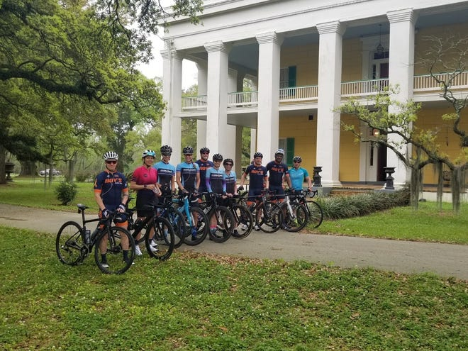 The bicycle group poses for a photo in front of Ashland Belle Helene Plantation.