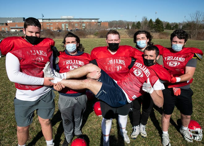 Bridgewater-Raynham Regional High School football offensive linemen from left to right Dominic Silva, Billy Donnelly, Ryan MacDermott, Max Compton, and Luke Payton hold up running back Anthony Morrison for a photograph during practice on Monday, March 29, 2021.