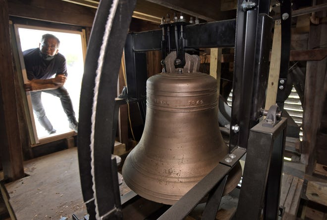 Chris Bodor, the chair for the Trinity Parish bicentennial celebration, looks at the church's recently restored 1842 bell.