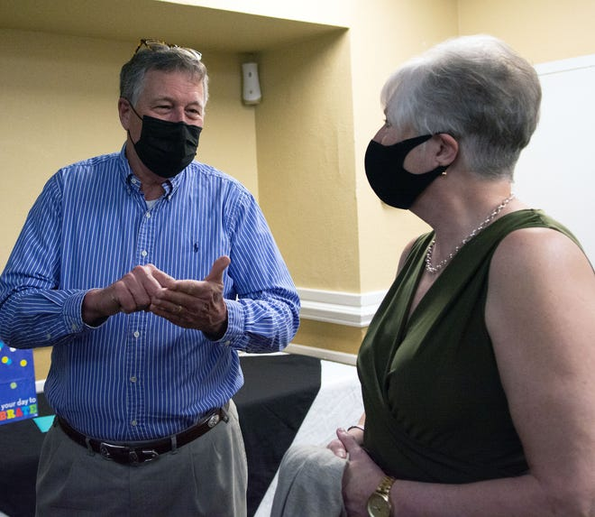 Gary Heiseys, a retired director of the Small Business Center at Blue Ridge Community College, chats with retiring Henderson County Tourism Development Authority Executive Director Beth Carden during a reception held Tuesday evening at The Cascades Mountain Resort.