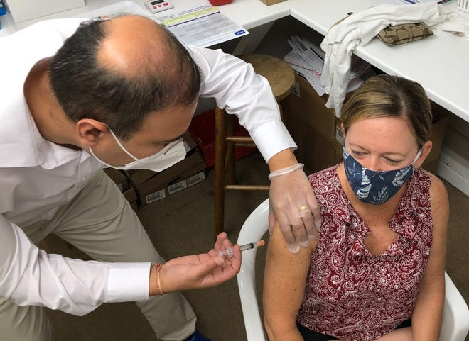 Peter Patel, owner and pharmacist at Cleveland Heights Pharmacy in Lakeland, gives Pam Hoffman a Moderna COVID-19 vaccine on Wednesday.