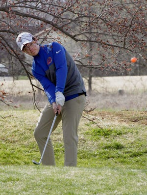 Moberly High School freshman Chase Nelson stands between tree limbs as he places his chip shot toward the green on hole no. 13 Tuesday at Heritage Hills Golf Course. Nelson turned in a score of 62 while playing the back nine holes, and the Spartans team lost its home dual to Boonville 234-245.