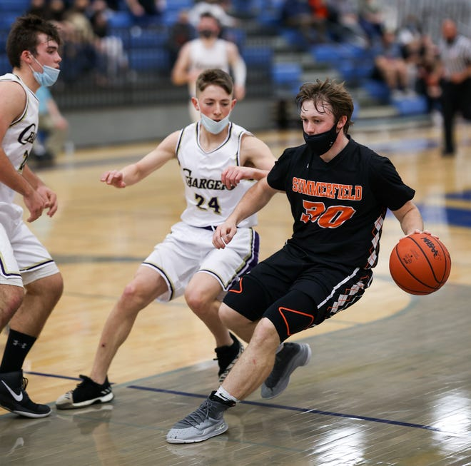Summerfield's Brock Olmstead is stopped by the Allen Park Inter-City Baptist defense led by Joshua Puga. Inter-City won the Regional semifinal game 52-51 Tuesday night.