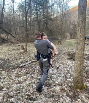 Trooper Brian Hotchkiss is seen carrying the missing 2-year old in his arm after rescuing her from the top of a Bristol mountain about half a mile from her home on County Road 33 in South Bristol.