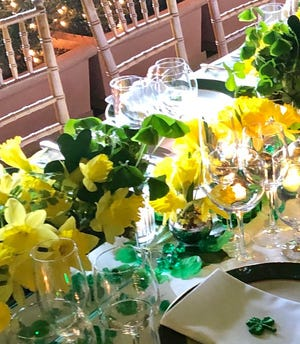 A springtime dining table is set with arrangements of daffodils for a gathering hosted by Palm Beach real estate agent Ite O'Higgins Young.