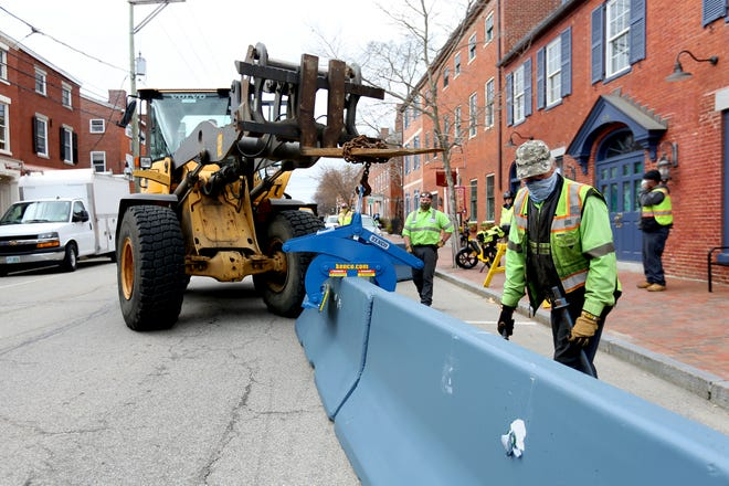 Workers place cement barriers for outdoor dining in front of Mr. Kim's on State Street Wednesday morning, March 31, 2021, in Portsmouth.