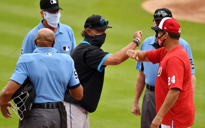 Miami Marlins manager Don Mattingly, left, greets Washington Nationals bench coach Tim Bogar before a spring training game at Ballpark of the Palm Beaches . [Jim Rassol-USA TODAY Sports]