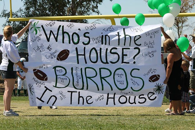 Supporters of the 2010 Burros sophomore team hold up a sign for the boys to run through before the youth athletes take the field.