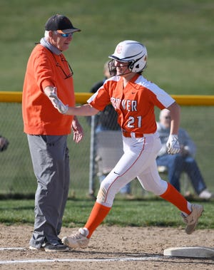 Hoover head coach Jerry Goodpasture slaps hands with Tess Bucher as she rounds third base to score in a game against GlenOak on Tuesday.