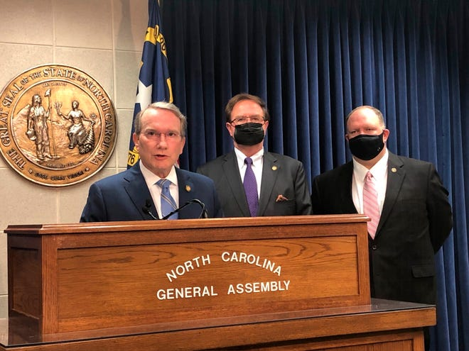 Paul Newton, R-Cabarrus, left, speaks while Sens. Chuck Edwards, R-Henderson, center, and Ralph Hise, R-Mitchell, stand at a news conference at the Legislative Building in Raleigh, N.C. on Wednesday, March 31, 2021. Newton is a primary sponsor of an elections measure heard in a Senate committee later Wednesday that in part would adjust deadlines to request absentee ballots and to turn them in to county election offices (AP Photo/Gary D. Robertson)