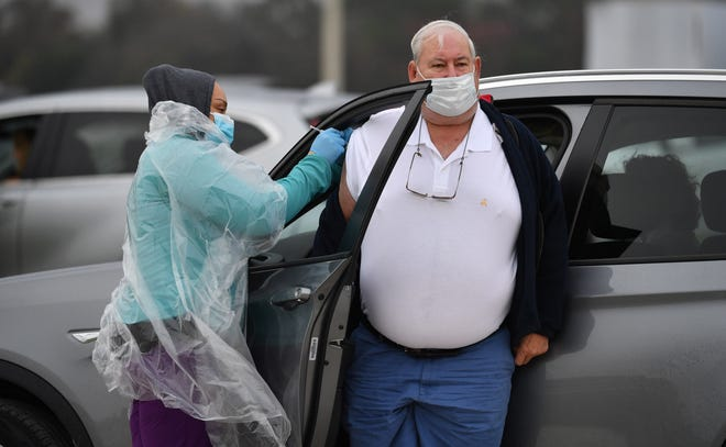 A driver gets out of his car so he can get a vaccination in his right arm at a vaccine pop-up clinic staged by state health officials in Lakewood Ranch. The clinic in a community developed by a donor to Gov. Ron DeSantis limited vaccine access to residents of two wealthy ZIP codes, provoking public outrage.