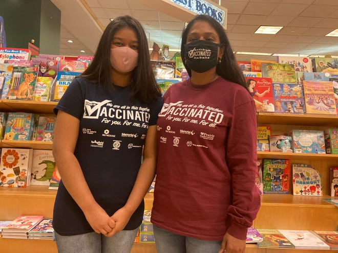 """Aliyah Hashmi, left, and her mother, Dr. Sayeeda Azra Jabeen, a hospitalist/internist at HSHS St. John's Hospital in Springfield, model """"Vaccinated"""" shirts that Hashmi, a freshman at Springfield High School, designed. Proceeds from sales of the shirts and masks will benefit the Central Illinois Foodbank and micropantries in Sangamon County. [Steven Spearie/The State Journal-Register]"""