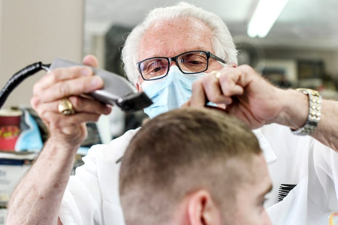 FILE - In this May 6, 2020 file photo, Karl Manke cuts hair in Owosso, Mich. The Michigan barber who defied Gov. Gretchen Whitmer and reopened his shop last spring during the coronavirus pandemic was fined $9,000 for violating licensing rules. (AP Photo /Lansing State Journal via AP)