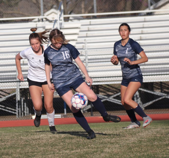 Shawnee's Sydnie Barry (16) tries to settle the soccer ball as teammate Michaela Pearne (1) runs and looks on in the background against Tulsa Bishop Kelley Tuesday night at Jim Thorpe Stadium. Bishop Kelley won the match, 10-0. Lady Wolves' goalkeeper Emma Wallace made 13 saves.
